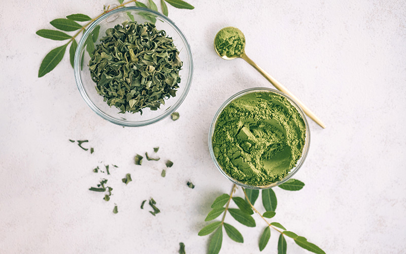 Two glass bowls seen from above: One has dried leaves, the other a green powder. For moringa benefits, facts, and use, read on.