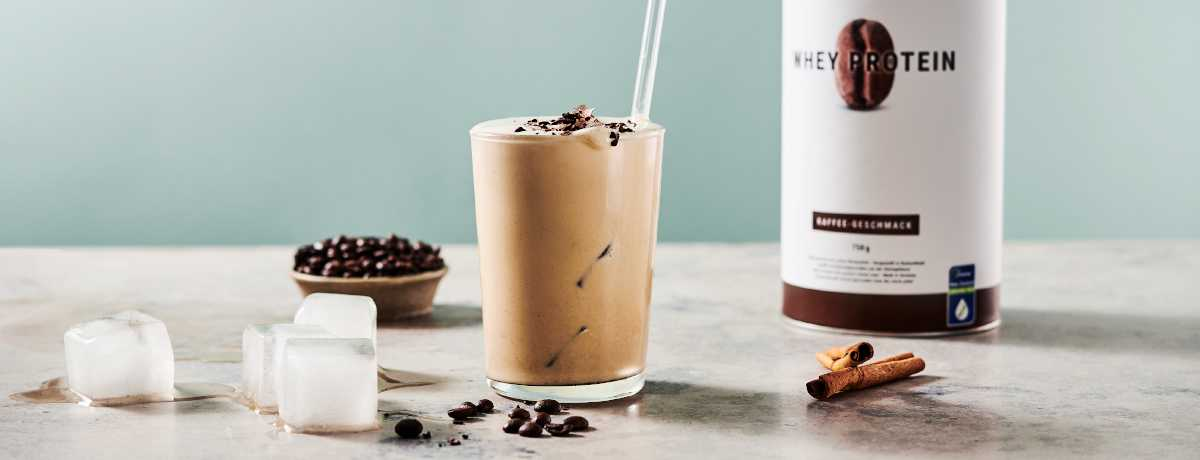 A glass of iced coffee protein shake sits with a glass straw sticking out of it. In front of the glass are a few coffee beans. Behind the glass, a canister of Coffee Whey Protein.