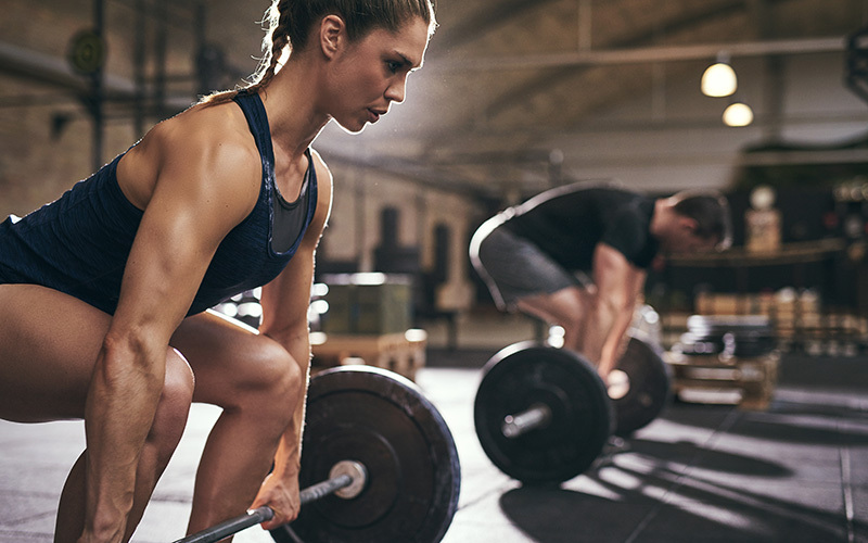 Two weight lifters, a man and a woman, make use of BCAA as they lift heavy barbells in a gym