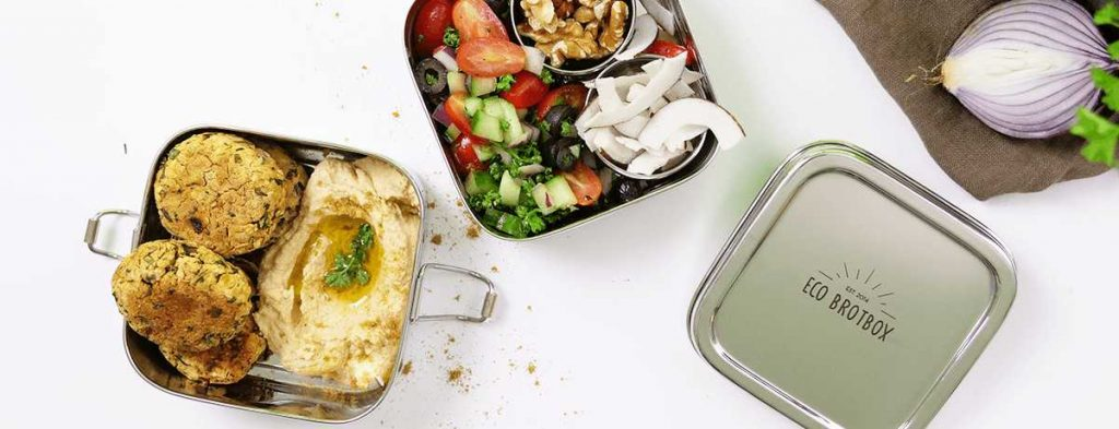 A stainless steel lunch box packed with hummus, falafel, and a tomato-cucumber salad