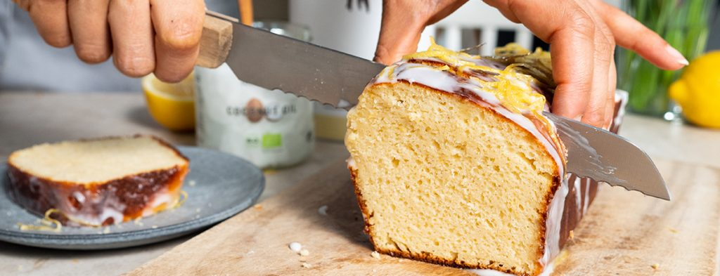 a medium-skin-toned hand holds a lemon cake gently while using a bread knife to slice off a piece.
